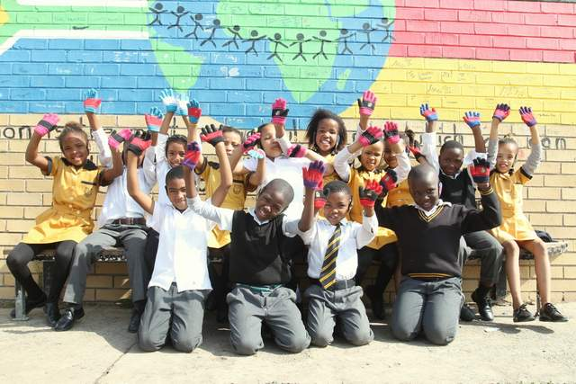 WARM HEARTS: Pupils at Parkside Primary show off their new gloves and ear muffs donated by the mosque next to the school to keep children warm in the winter chill. The pupils returned to school again last week after its closure due to severe vandalism Picture: SARAH KINGON