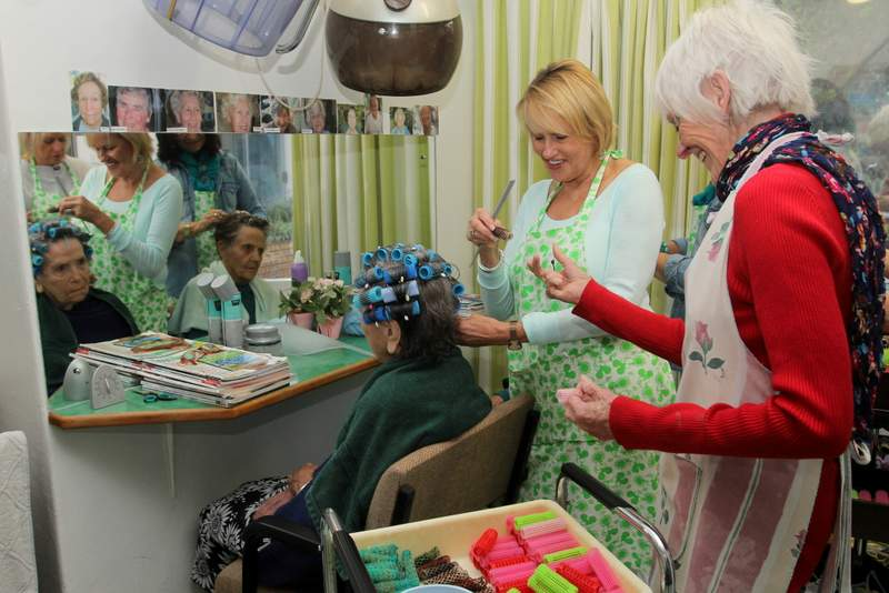 GOOD MEDICINE: Residents, from left, Brenda Fitzpatrick and Esmé Swart have their hair done by Beacon Bay  Rotary  Anns' Maureen Dalbock, centre, and Anne Baker, at Salon Joan in  Kennersley   Park  this week Picture: SARAH KINGON